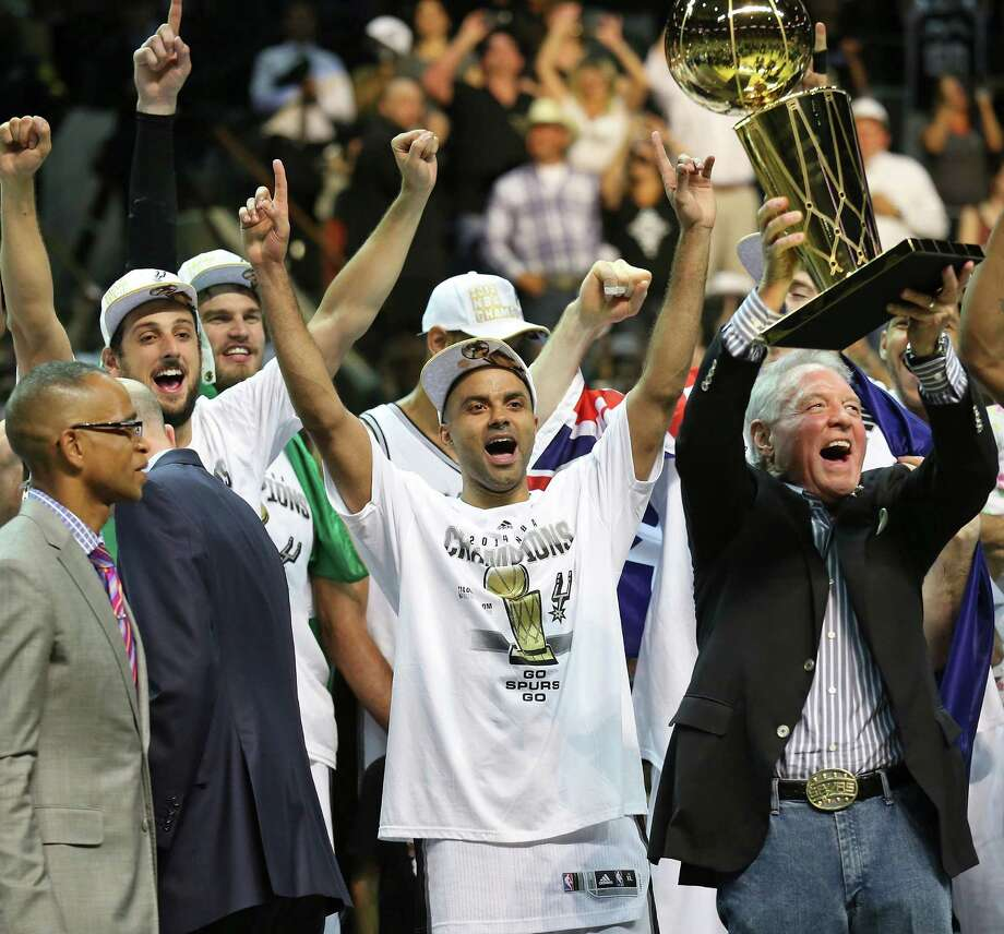 Spurs owner Peter Holt hoists the trophy as (from left) Marco Belinelli, Tiago Splitter, Tony Parker and other Spurs celebrate the franchise's fifth NBA title and first since 2007. Photo: Edward A. Ornelas / San Antonio Express-News / © 2014 San Antonio Express-News