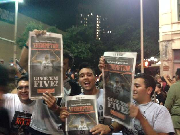 Spurs fans hold up copies of the San Antonio Express-News' Extra edition downtown after the Spurs won their fifth title on Sunday, June 15, 2014. Photo: Rebecca Salinas/San Antonio Express-News