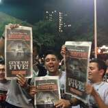 Spurs fans hold up copies of the San Antonio Express-News' Extra edition downtown after the Spurs won their fifth title on Sunday, June 15, 2014.