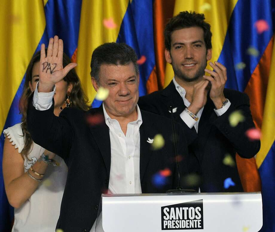 "President Juan Manuel Santos, celebrating his re-election, shows his palm with the word ""peace."" Photo: Guillermo Legaria, AFP/Getty Images"