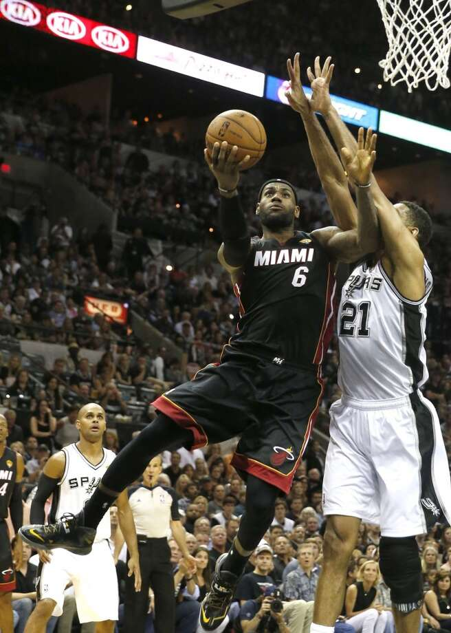 LeBron James is pushed away from the basket by Tim Duncan in the second quarter in Game 5. Photo: CHARLES TRAINOR JR, McClatchy-Tribune News Service