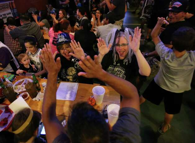 Gloria Padilla, center left, and Emily New, center right, high-five New's husband, Robert Mercado, bottom, after a point by the Spurs during Game 5 of the NBA Finals on Sunday, June 15, 2014, at Fatso's Sports Garden in San Antonio. General manager Jim Woods estimated about 500 customers were present to watch the game. Photo: Timothy Tai, Express-News Staff / © 2014 San Antonio Express-News