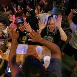 Gloria Padilla, center left, and Emily New, center right, high-five New's husband, Robert Mercado, bottom, after a point by the Spurs during Game 5 of the NBA Finals on Sunday, June 15, 2014, at Fatso's Sports Garden in San Antonio. General manager Jim Woods estimated about 500 customers were present to watch the game.