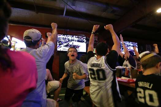 John Arredondo, 12, center, reacts after a point by the Spurs during Game 5 of the NBA Finals on Sunday, June 15, 2014, at Fatso's Sports Garden in San Antonio. General manager Jim Woods estimated about 500 customers were present to watch the game. Photo: Timothy Tai, Express-News Staff / © 2014 San Antonio Express-News