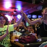 Emma King, left, high-fives her sister, Charity Rivera, on Sunday, June 15, 2014, at Fatso's Sports Garden in San Antonio. Rivera said the two have been coming to Fatso's to watch NBA championship games since 1999.