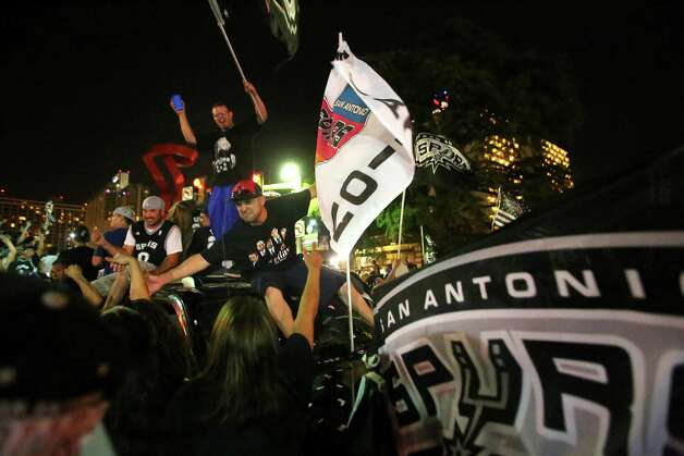 Fans celebrate in downtown San Antonio on Sunday, June 15, 2014, after the Spurs defeated the Miami Heat to win the NBA Championship. Photo: Timothy Tai, Express-News Staff / © 2014 San Antonio Express-News