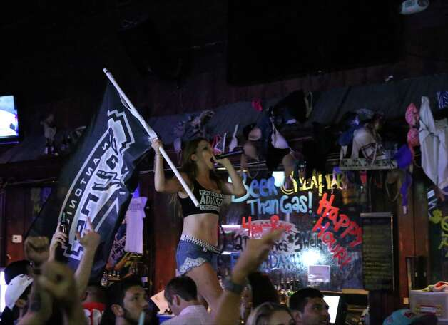 A dancer amps up the crowd with a Spurs flag while watching Game 5 of the NBA Finals on Sunday, June 15, 2014, at Coyote Ugly Saloon in San Antonio. Photo: Timothy Tai, Express-News Staff / © 2014 San Antonio Express-News