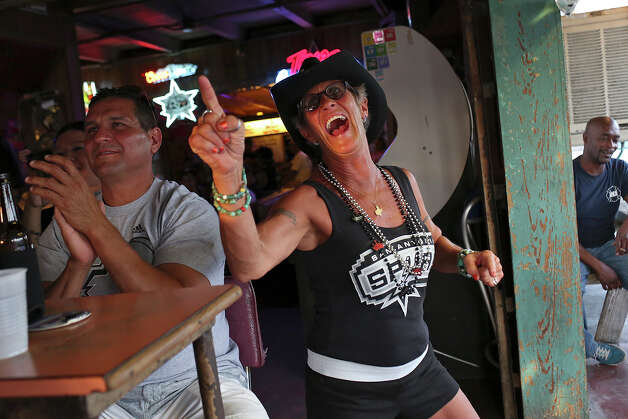 Tina Sutter shows her Spurs spirit as she watches the game with friends including Jay Sanchez, left, at Texas Ice Service, an icehouse on Blanco Road, as the Spurs play the Miami Heat during Game 5 of the NBA Finals in San Antonio on Sunday, June 15, 2014. Photo: Lisa Krantz, Express-News Staff / SAN ANTONIO EXPRESS-NEWS