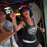 Tina Sutter shows her Spurs spirit as she watches the game with friends including Jay Sanchez, left, at Texas Ice Service, an icehouse on Blanco Road, as the Spurs play the Miami Heat during Game 5 of the NBA Finals in San Antonio on Sunday, June 15, 2014.