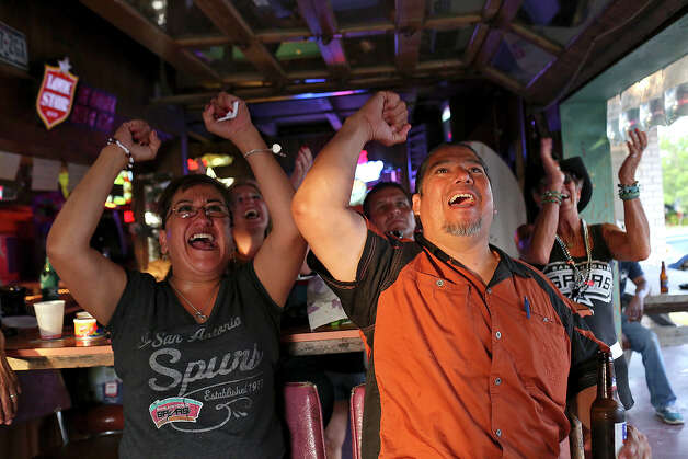 Leticia Garza, left, and her boyfriend, Robert Lopez, cheer for the Spurs at Texas Ice Service, an icehouse on Blanco Road, as they watch the Spurs play the Miami Heat during Game 5 of the NBA Finals in San Antonio on Sunday, June 15, 2014. Photo: Lisa Krantz, Express-News Staff / SAN ANTONIO EXPRESS-NEWS
