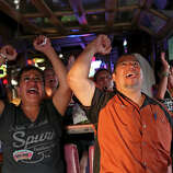 Leticia Garza, left, and her boyfriend, Robert Lopez, cheer for the Spurs at Texas Ice Service, an icehouse on Blanco Road, as they watch the Spurs play the Miami Heat during Game 5 of the NBA Finals in San Antonio on Sunday, June 15, 2014.