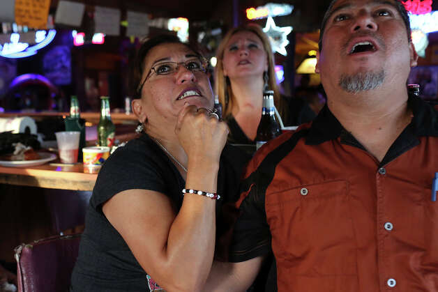 Leticia Garza, left, agonizes over a play with her boyfriend, Robert Lopez, at Texas Ice Service, an icehouse on Blanco Road, as they watch the Spurs play the Miami Heat during Game 5 of the NBA Finals in San Antonio on Sunday, June 15, 2014. Photo: Lisa Krantz, Express-News Staff / SAN ANTONIO EXPRESS-NEWS