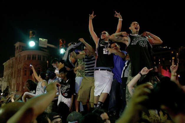 Fans celebrate the Spurs winning the NBA Championship after beating the Miami Heat as they stand on top of a car on Commerce Street in downtown San Antonio on Sunday, June 15, 2014 Photo: Lisa Krantz, Express-News Staff / SAN ANTONIO EXPRESS-NEWS