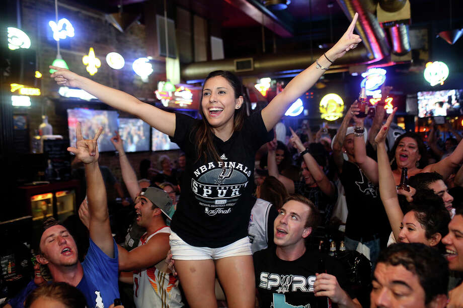 Keep clicking to view more photos of Spurs fans celebrating the team's fifth NBA title.Melissa Riojas celebrates the Spurs winning the NBA Championship after beating the Miami Heat at Ticket Sports Pub in downtown San Antonio on Sunday, June 15, 2014. Photo: Lisa Krantz, Express-News Staff / SAN ANTONIO EXPRESS-NEWS