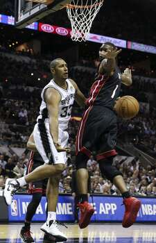 San Antonio Spurs' Boris Diaw passes the ball under Miami Heat's Chris Bosh during first half action in Game 5 of the 2014 NBA Finals Sunday June 15, 2014 at the AT&T Center. Photo: Edward A. Ornelas, San Antonio Express-News