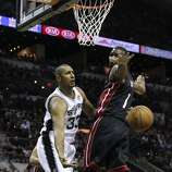 San Antonio Spurs' Boris Diaw passes the ball under Miami Heat's Chris Bosh during first half action in Game 5 of the 2014 NBA Finals Sunday June 15, 2014 at the AT&T Center.