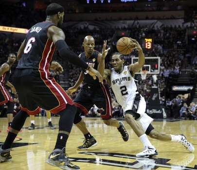San Antonio Spurs' Kawhi Leonard drives towards the basket around Miami Heat's LeBron James and Ray Allen  during first half action in Game 5 of the 2014 NBA Finals Sunday June 15, 2014 at the AT&T Center. Photo: Edward A. Ornelas, San Antonio Express-News