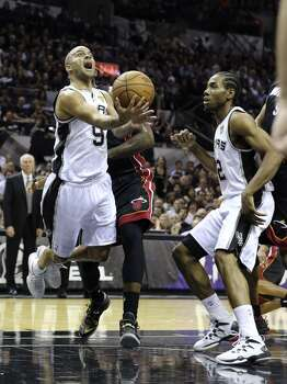 San Antonio Spurs' Tony Parker gets tripped up by Miami Heat's LeBron James while driving to the basket during first half action in Game 5 of the 2014 NBA Finals Sunday June 15, 2014 at the AT&T Center. Photo: Edward A. Ornelas, San Antonio Express-News