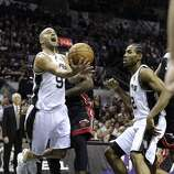 San Antonio Spurs' Tony Parker gets tripped up by Miami Heat's LeBron James while driving to the basket during first half action in Game 5 of the 2014 NBA Finals Sunday June 15, 2014 at the AT&T Center.