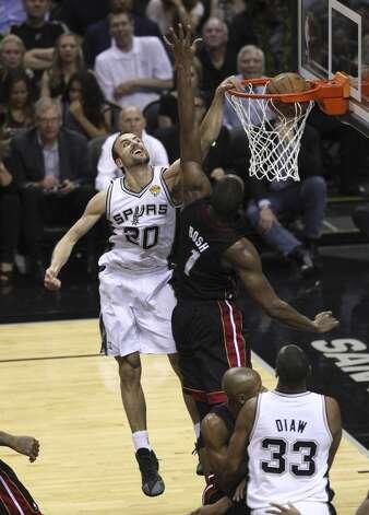San Antonio Spurs' Manu Ginobili dunks over Miami Heat's Chris Bosh in the second quarter of Game 5 of the 2014 NBA Finals at the AT&T Center on Sunday, June 15, 2014. (Kin Man Hui/San Antonio Express-News) Photo: Kin Man Hui, San Antonio Express-News