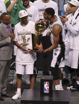 San Antonio Spurs' Tim Duncan (right) playfully takes away the O'Brien trophy from teammate Tony Parker after winning Game 5 against the Miami Heat at the 2014 NBA Finals at the AT&T Center on Sunday, June 15, 2014. (Kin Man Hui/San Antonio Express-News) Photo: Kin Man Hui, San Antonio Express-News