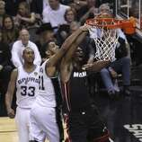 San Antonio Spurs' Tim Duncan draws the foul on Miami Heat's Chris Bosh in the second  halfof Game 5 of the 2014 NBA Finals at the AT&T Center on Sunday, June 15, 2014. (Kin Man Hui/San Antonio Express-News)