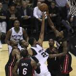 San Antonio Spurs' Tim Duncan takes a contested shot against Miami Heat's Udonis Haslem in the second quarter of Game 5 of the 2014 NBA Finals at the AT&T Center on Sunday, June 15, 2014. (Kin Man Hui/San Antonio Express-News)