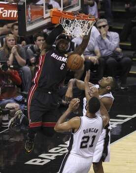 Miami Heat's LeBron James dunks over San Antonio Spurs' Boris Diaw and San Antonio Spurs' Tim Duncan in the first quarter of Game 5 of the 2014 NBA Finals at the AT&T Center on Sunday, June 15, 2014. (Kin Man Hui/San Antonio Express-News) Photo: Kin Man Hui, San Antonio Express-News