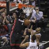 Miami Heat's LeBron James dunks over San Antonio Spurs' Boris Diaw and San Antonio Spurs' Tim Duncan in the first quarter of Game 5 of the 2014 NBA Finals at the AT&T Center on Sunday, June 15, 2014. (Kin Man Hui/San Antonio Express-News)