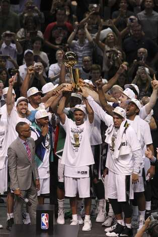 The San Antonio Spurs hold up the O'Brien Trophy after winning Game 5 against the Miami Heat at the 2014 NBA Finals at the AT&T Center on Sunday, June 15, 2014. (Kin Man Hui/San Antonio Express-News) Photo: Kin Man Hui, San Antonio Express-News
