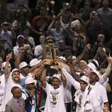 The San Antonio Spurs hold up the O'Brien Trophy after winning Game 5 against the Miami Heat at the 2014 NBA Finals at the AT&T Center on Sunday, June 15, 2014. (Kin Man Hui/San Antonio Express-News)