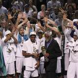 San Antonio Spurs' Kawhi Leonard accepts the Most Valuable Player trophy from NBA legend Bill Russell after the Spurs defeat the Miami Heat in Game 5 of the 2014 NBA Finals at the AT&T Center on Sunday, June 15, 2014. (Kin Man Hui/San Antonio Express-News)
