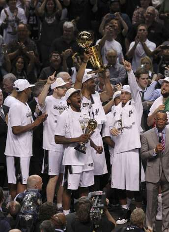 San Antonio Spurs' Kawhi Leonard reacts as teammate Jeff Ayres hold up the O'Brien trophy after the Spurs win Game 5 against the Miami Heat at the 2014 NBA Finals at the AT&T Center on Sunday, June 15, 2014. (Kin Man Hui/San Antonio Express-News) Photo: Kin Man Hui, San Antonio Express-News