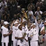 San Antonio Spurs' Kawhi Leonard reacts as teammate Jeff Ayres hold up the O'Brien trophy after the Spurs win Game 5 against the Miami Heat at the 2014 NBA Finals at the AT&T Center on Sunday, June 15, 2014. (Kin Man Hui/San Antonio Express-News)