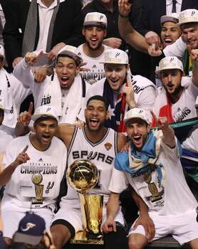 The San Antonio Spurs pose with the O'Brien Trophy after winning Game 5 against the Miami Heat at the 2014 NBA Finals at the AT&T Center on Sunday, June 15, 2014. (Kin Man Hui/San Antonio Express-News) Photo: Kin Man Hui, San Antonio Express-News