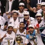 The San Antonio Spurs pose with the O'Brien Trophy after winning Game 5 against the Miami Heat at the 2014 NBA Finals at the AT&T Center on Sunday, June 15, 2014. (Kin Man Hui/San Antonio Express-News)