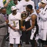 San Antonio Spurs' Tim Duncan (right) playfully takes away the O'Brien trophy from teammate Tony Parker after winning Game 5 against the Miami Heat at the 2014 NBA Finals at the AT&T Center on Sunday, June 15, 2014. (Kin Man Hui/San Antonio Express-News)