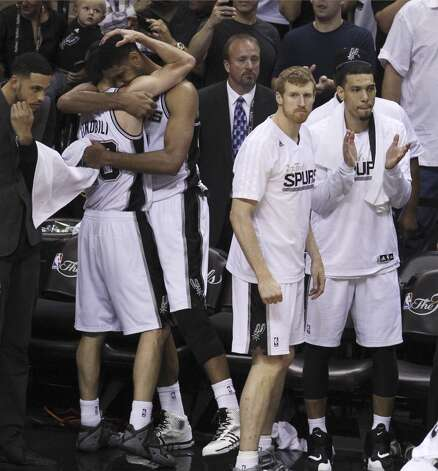 San Antonio Spurs' Manu Ginobili receives a hug from Tim Duncan in the closing moments of Game 5 as the Spurs defeat the Miami Heat in the 2014 NBA Finals at the AT&T Center on Sunday, June 15, 2014. (Kin Man Hui/San Antonio Express-News) Photo: Kin Man Hui, San Antonio Express-News