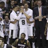 San Antonio Spurs' Danny Green (left) and Tiago Splitter congratulate Tony Parker in the closing moments of Game 5 against the Miami Heat to win the 2014 NBA Finals at the AT&T Center on Sunday, June 15, 2014. (Kin Man Hui/San Antonio Express-News)