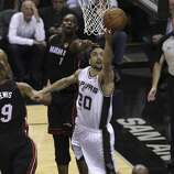 San Antonio Spurs' Manu Ginobili drives on a shot Miami Heat's Chris Bosh in Game 5 of the 2014 NBA Finals at the AT&T Center on Sunday, June 15, 2014. (Kin Man Hui/San Antonio Express-News)