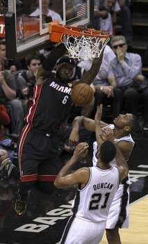 Miami Heat's LeBron James dunks over San Antonio Spurs' Boris Diaw and San Antonio Spurs' Tim Duncan in the first quarter of Game 5 of the 2014 NBA Finals at the AT&T Center on Sunday, June 15, 2014. (Kin Man Hui/San Antonio Express-News) Photo: San Antonio Express-News