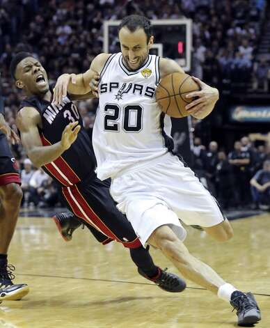 San Antonio Spurs' Manu Ginobili looks for room around Miami Heat's Norris Cole during first half action in Game 5 of the 2014 NBA Finals Sunday June 15, 2014 at the AT&T Center. Photo: San Antonio Express-News