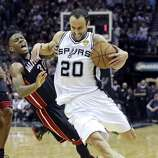 San Antonio Spurs' Manu Ginobili looks for room around Miami Heat's Norris Cole during first half action in Game 5 of the 2014 NBA Finals Sunday June 15, 2014 at the AT&T Center.