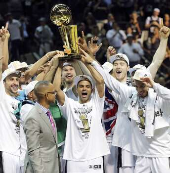 Members of the Spurs hold the trophy after Game 5 of the 2014 NBA Finals against the Miami Heat Sunday June 15, 2014 at the AT&T Center. The Spurs won 104-87. Photo: San Antonio Express-News