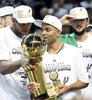 San Antonio Spurs' Boris Diaw (left) and San Antonio Spurs' Tony Parker  look at the trophy after Game 5 of the 2014 NBA Finals against the Miami Heat Sunday June 15, 2014 at the AT&T Center. The Spurs won 104-87. Photo: San Antonio Express-News