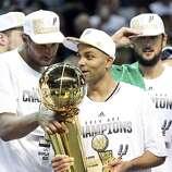San Antonio Spurs' Boris Diaw (left) and San Antonio Spurs' Tony Parker  look at the trophy after Game 5 of the 2014 NBA Finals against the Miami Heat Sunday June 15, 2014 at the AT&T Center. The Spurs won 104-87.