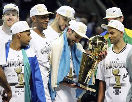 San Antonio Spurs' Manu Ginobili and teammates look at the trophy after Game 5 of the 2014 NBA Finals against the Miami Heat Sunday June 15, 2014 at the AT&T Center. The Spurs won 104-87. Photo: San Antonio Express-News