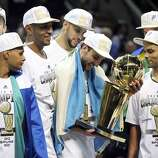 San Antonio Spurs' Manu Ginobili and teammates look at the trophy after Game 5 of the 2014 NBA Finals against the Miami Heat Sunday June 15, 2014 at the AT&T Center. The Spurs won 104-87.