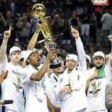 San Antonio Spurs' Kawhi Leonard (center) hold the MVP Trophy while celebrating with teammates after Game 5 of the 2014 NBA Finals against the Miami Heat Sunday June 15, 2014 at the AT&T Center. The Spurs won 104-87.