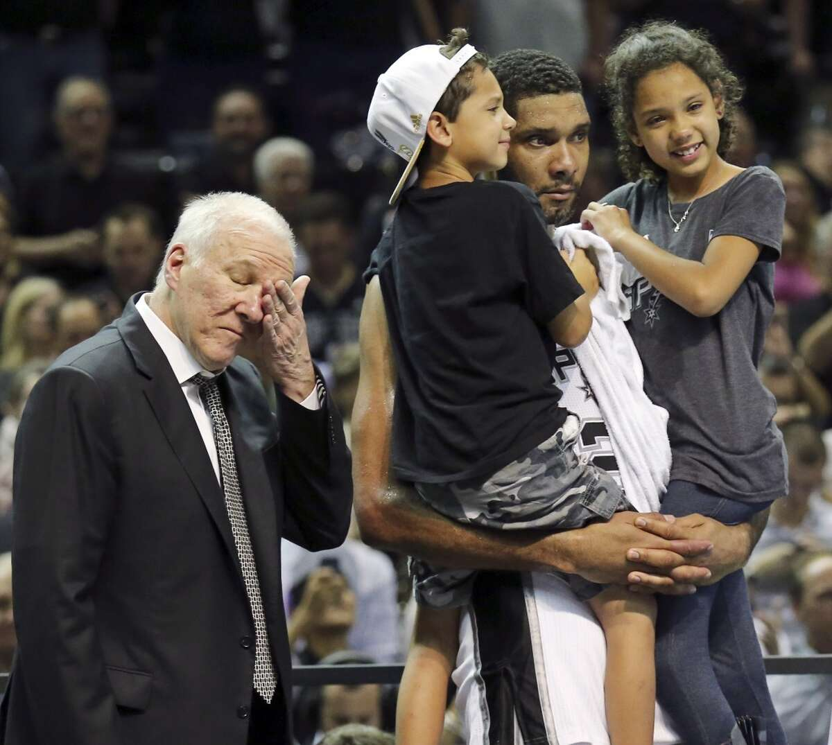 San Antonio Spurs' Tim Duncan holds his children Draven (left) and Sydney as head coach Gregg Popovich wipes away tears after Game 5 of the 2014 NBA Finals against the Miami Heat Sunday June 15, 2014 at the AT&T Center. The Spurs won 104-87.